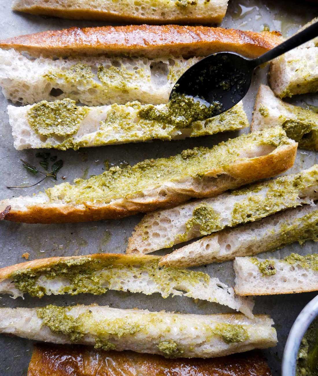 Skær brødet i aflange stænger / pinde. Smør dem med pesto og ost