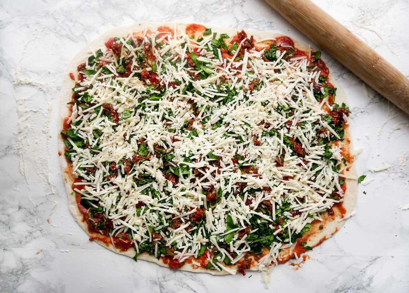 Fold pizzadejen ud og tilsæt tomatsauce, fyld og ost