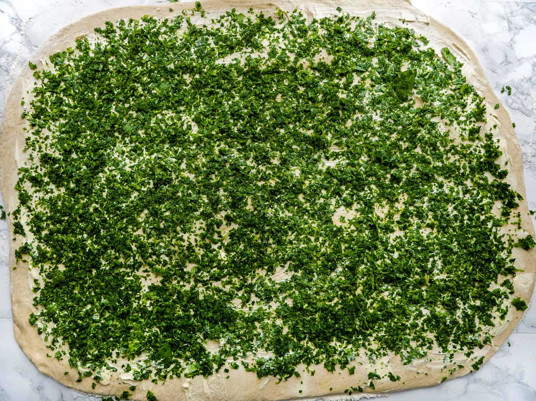 Rul dejen ud og drys med finthakket spinatblade